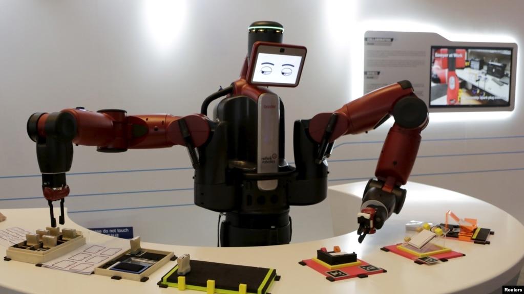 在中國大連舉行的世界經濟論壇會議上,機器人表演拿名片(2015年9月9日)