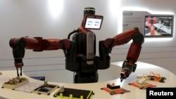 在中国大连举行的世界经济论坛会议上,机器人表演拿名片(2015年9月9日)