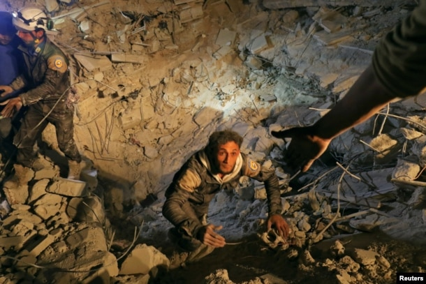 A civil defense member attempts to get out of a site hit at night by an airstrike in Saraqeb, in rebel-held Idlib province, Syria, Dec. 11, 2016.