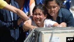 Jessica pleure à l'arrivée du cercueil de sa soeur, une domestique dont le corps a été retrouvé dans un congélateur au Koweit, Aéroport de Manille, Philippines, 16 février 2018.