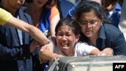 Jessica (tengah), saudara perempuan TKW asal Filipina, Joanna Demafelis, yang jenazah ditemukan di dalam lemari pendingin di Kuwait, menangis di depan peti jenazah yang berisi tubuh saudaranya, tak lama setelah tiba di bandara internasional Manila, 16 Februari 2018.