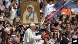 Đức Giáo Hoàng Phanxicô đi ngang qua phía trước bức ảnh Mẹ Teresa tại quảng trường Thánh Phêrô Vatican, ngày 4 tháng 9 năm 2016.
