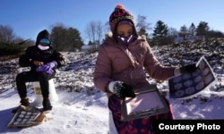 Siswa 4 SD, Falis Asair sedang mempelajari kepingan salju saat pembelajaran luar ruang di Maine (AP: Robert F. Bukaty)