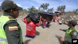 Policías colombianos observan el paso de colombianos deportados que cruzan el río Táchira en la frontera con Venezuela.