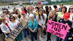 FILE - A group of women hold signs and shout their support as they wait on line to attend a Republican presidential candidate, Donald Trump campaign rally, in Wilkes-Barre, Pennsylvania, April 25, 2016.