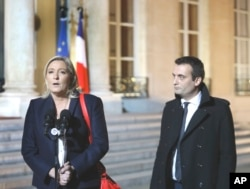 French far-right party leader Marine Le Pen , left, addresses the media with Florian Philippot after a meeting with French President Francois Hollande in Paris, Nov. 15, 2015.