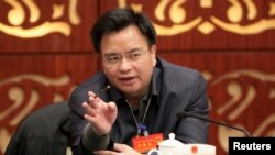 FILE - Wan Qingliang, then Communist Party Secretary of Guangzhou, gestures as he speaks at a meeting in Guangzhou, February 18, 2014.