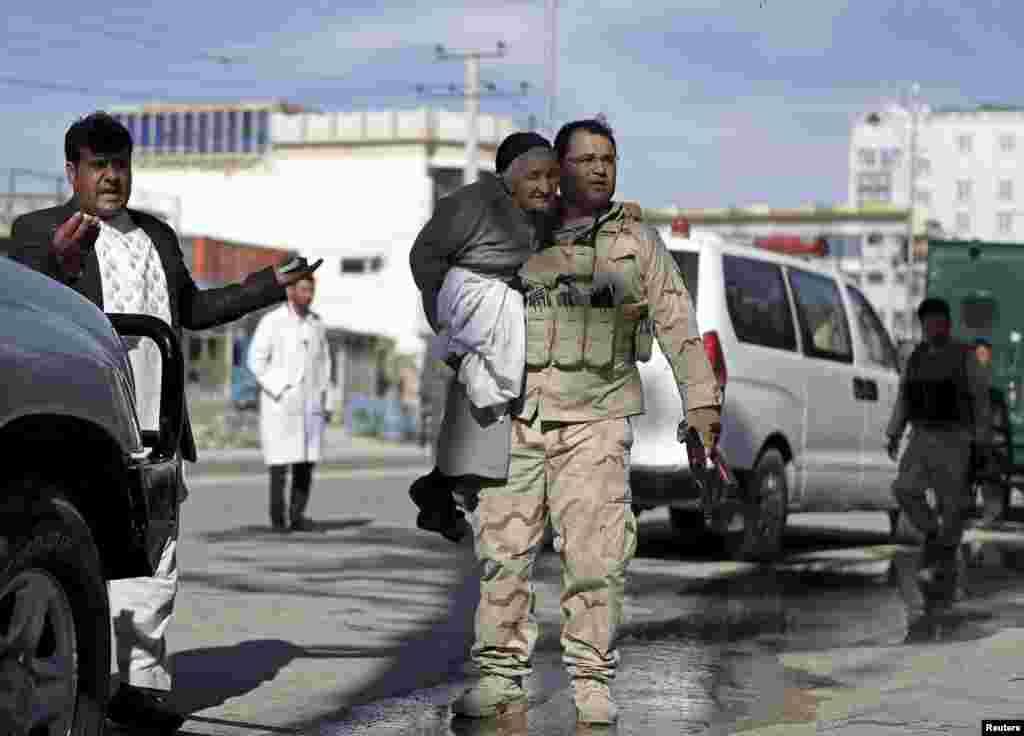 Seorang anggota pasukan keamanan Afghanistan menggendong seorang perempuan ketika menyelamatkannya dari lokasi serangan di Mazar-i-Sharif. Para militan yang bersenjatakan granat roket dan senjata lainnya menyerbu sebuah pengadilan di kota tersebut, menewaskan kepala polisi distrik dan dua polisi lainnya, menurut pihak berwenang.