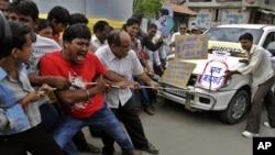 Indian people pull a car by rope and shout slogans during a protest against the price hike in diesel and capping the number of subsidized cooking gas cylinders in Ahmadabad, India, September 14, 2012.