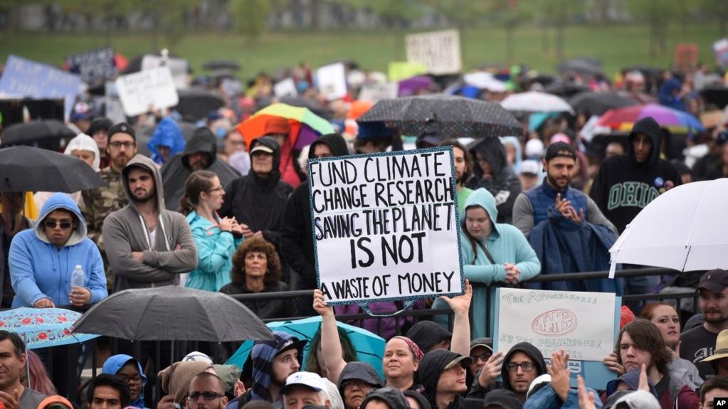 """Biểu ngữ ghi """"hãy tài trợ cho nghiên cứu biến đổi khí hậu. Cứu Trái đất không phải là phung phí tiền bạc"""" tại cuộc Tuần hành vì Khoa học 22/4"""