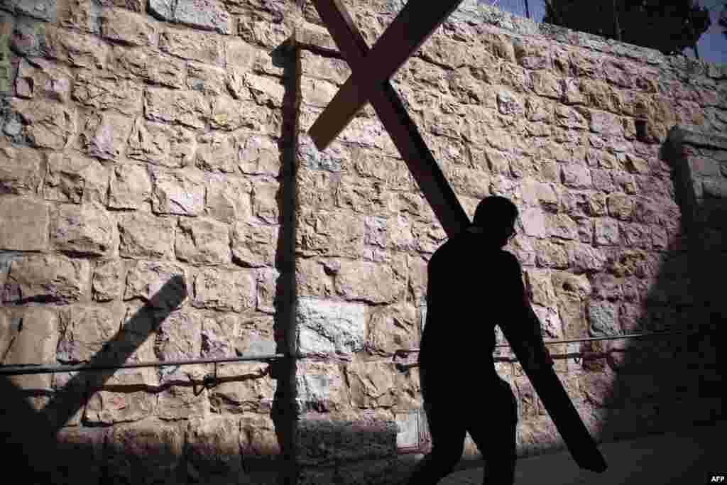 Seorang peziarah Katolik membawa kayu salib melewati Via Dolorosa di kota tua Yerusalem pada prosesi Jumat Agung.