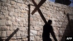 FILE: A Catholic pilgrim carries a wooden cross along the Via Dolorosa (Way of Suffering) in Jerusalem's Old City during the Good Friday procession, March 25, 2016.