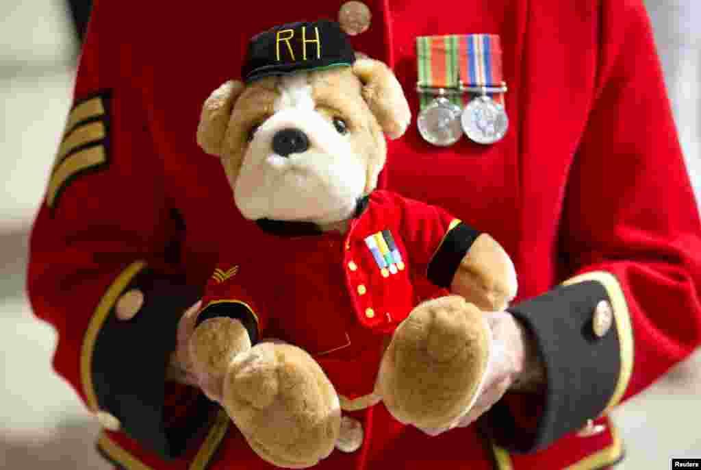 Pensionistas de Chelsea muestran un peluche con el tradicional uniforme escarlata, un regalo para el recién nacido príncipe de Cambridge.