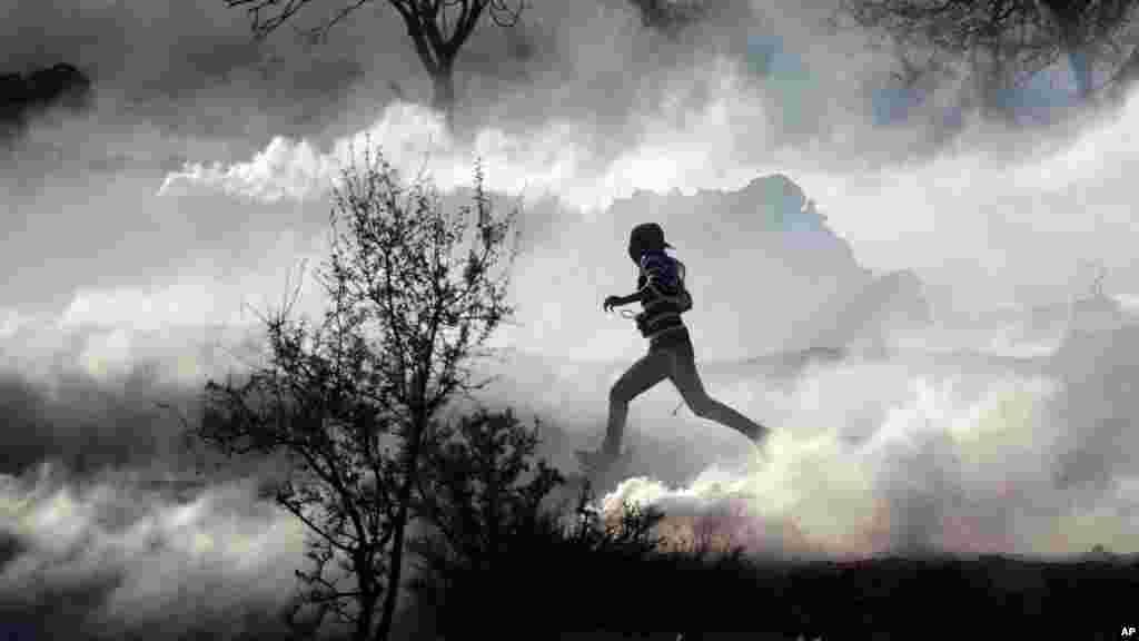 Un manifestant palestinien fuyant dans un nuage gaz lacrymogène près d'une prison militaire israélienne proche de Ramallah, en Cisjordanie