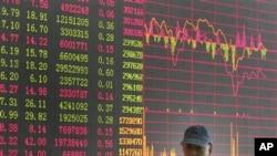 投資者走過上海證券公司的股市行情屏幕