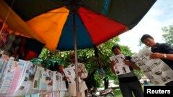 Warga Phnom Penh membaca berita-berita terkait pemilihan umum (10/8). (Reuters/Samrang Pring)