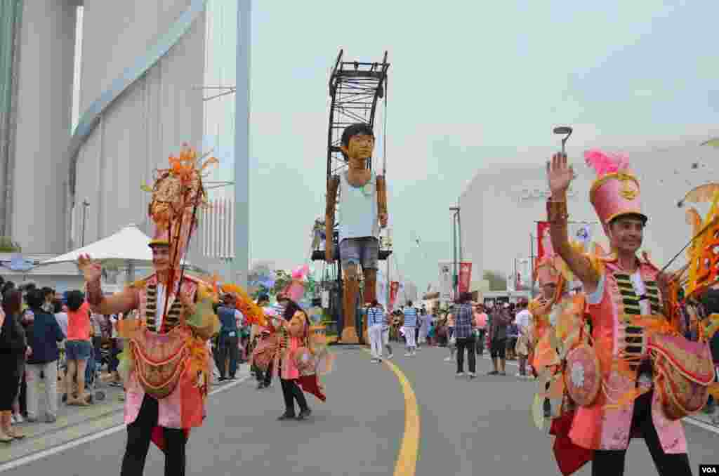 A parade with a giant marionette at the expo, Yeosu, South Korea, June 9, 2012. (S.L. Herman/VOA)