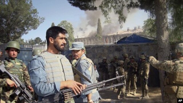 Afghan policemen, U.S. and Afghan soldiers on alert near the police traffic department building, which was under attack by insurgents in Khost, eastern of Afghanistan, May 22, 2011