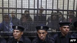 Cảnh sát ngồi phía trước khu có rào lưới bên trong là các nhân viên của nhiều nhóm cổ võ cho dân chủ, tại phiên tòa ở Cairo, 26/2/2012