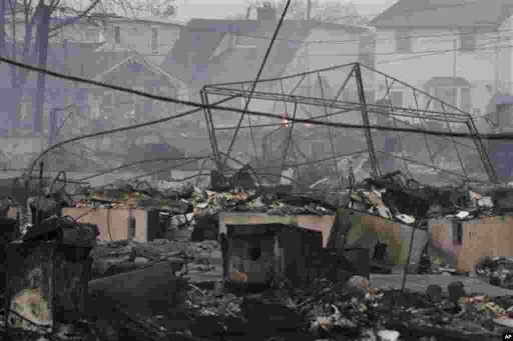 2012年10月30日,被火烧毁的民宅余烬未熄。10月29日夜,纽约市皇后区一处社区因超级风暴桑迪来袭先遭水淹后又起火,有80到100所房屋被毁。