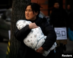 FILE - A mother carries her baby wrapped in a blanket in Beijing.