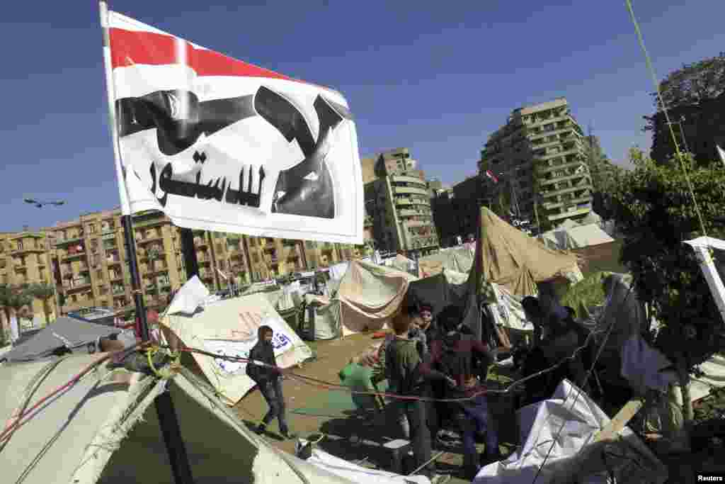 "Anti-Morsi protesters sit outside their tents, below a flag that reads, ""No, to Constitution,"" Tahrir Square, Cairo, Egypt, December 10, 2012."