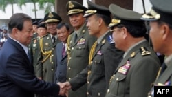 Thai Defense Minister General Yuthasak Sasiprapa, left, shakes hands with Cambodia's internal-security chief Sao Sokha, right, upon his arrival at the Ministry of Defense in Phnom Penh on Sept. 23, 2011.