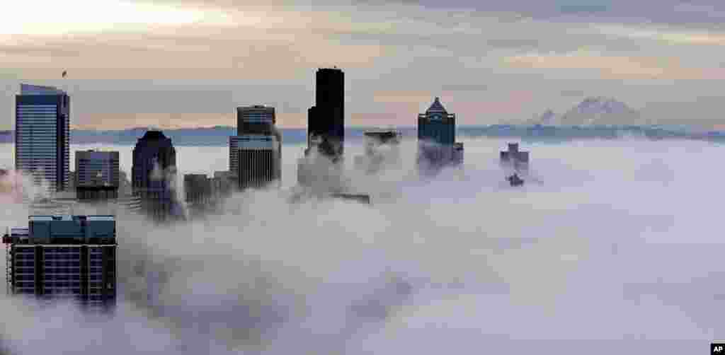 Downtown buildings rise above a low-level morning fog as Mount Rainier is seen some 80 miles in the distance, in this view from atop the Space Needle in Seattle.