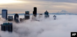 Downtown buildings rise above a low-level morning fog as Mount Rainier is seen some 80 miles distant, Jan. 9, 2015, in this view from atop the Space Needle in Seattle.