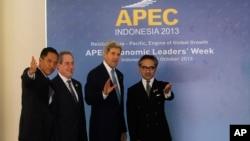 Menlu Indonesia Marty Natalegawa (kanan) dan Menteri Perdagangan Gita Wirjawan (kiri) menyambut Menlu AS John Kerry (dua dari kanan) dan Utusan Perdagangan AS Michael Froman setibanya di Bali untuk menghadiri Forum Kerjasama Ekonomi Asia Pasifik (APEC), 4 Oktober 2013 (AP Photo/Wang Maye-E).