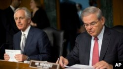 Senate Foreign Relations Committee Chairman Sen. Bob Corker, R-Tenn., left, and the committee's ranking member, Sen. Robert Menendez, D-NJ., prepare for the committee's hearing on Capitol Hill in Washington, March 11, 2015.