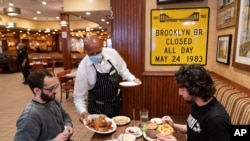 FILE - A waiter serves lunch at Junior's Restaurant in New York. NYC will soon require proof of COVID-19 vaccinations for anyone who wants to dine inside at a restaurant.