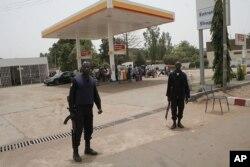 Des policiers montent la garde devant une station de carburant à Bamako (24 mars 2012)