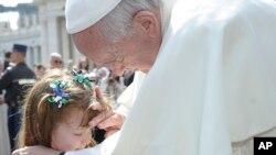 Le Pape François touche le visage de Lizzy Myers, 5 ans, de Bellville, Ohio, à la fin de l'audience générale sur la place Saint-Pierre au Vatican, le mercredi 6 Avril 2016. (L'Osservatore Romano / pool photo via AP)