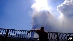 Un hombre mira hacia un volcán mientras continúa en erupción en la isla canaria de La Palma, España, el sábado 9 de octubre de 2021.