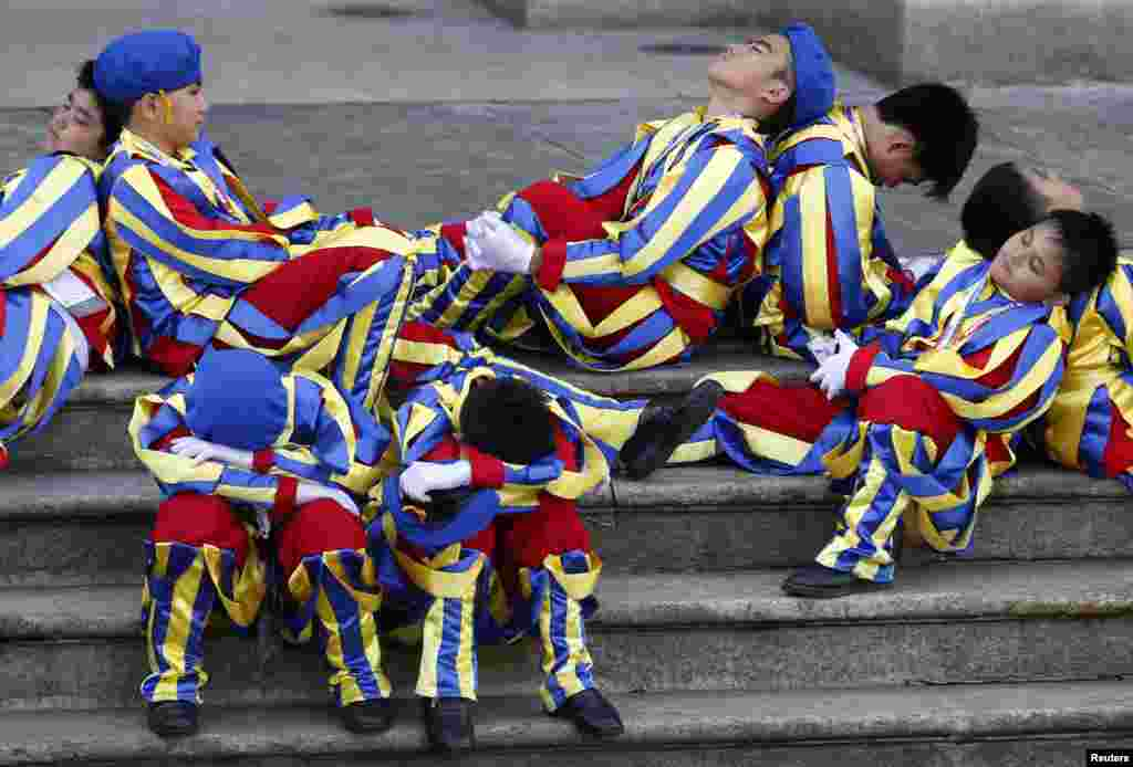 Schoolchildren dressed as Swiss Guards rest as they wait for the arrival of Pope Francis outside the Manila Cathedral in Manila, The Philippines.