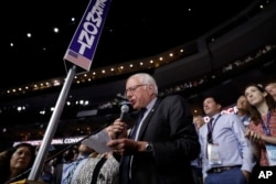 Former Democratic presidential candidate, Sen. Bernie Sanders, I-Vt., stands with the Vermont delegation and asks that Hillary Clinton become the unanimous choice for President of the United States during the second day of the Democratic National Convention.
