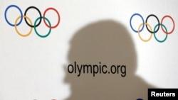 Bayangan Presiden Komite Olimpiade Internasional (IOC) Thomas Bach terpampang di dinding berlogo olimpiade saat konferensi pers usai pertemuan Dewan Eksekutif di Lausanne, Swiss, 8 Desember 2016. (Foto: dok).