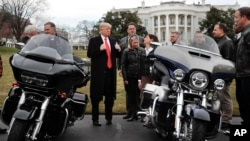 President Donald Trump give a 'thumbs-up' as he meets with Harley Davidson executives and union representatives on the South Lawn of the White House in Washington, Thursday, Feb. 2, 2017.