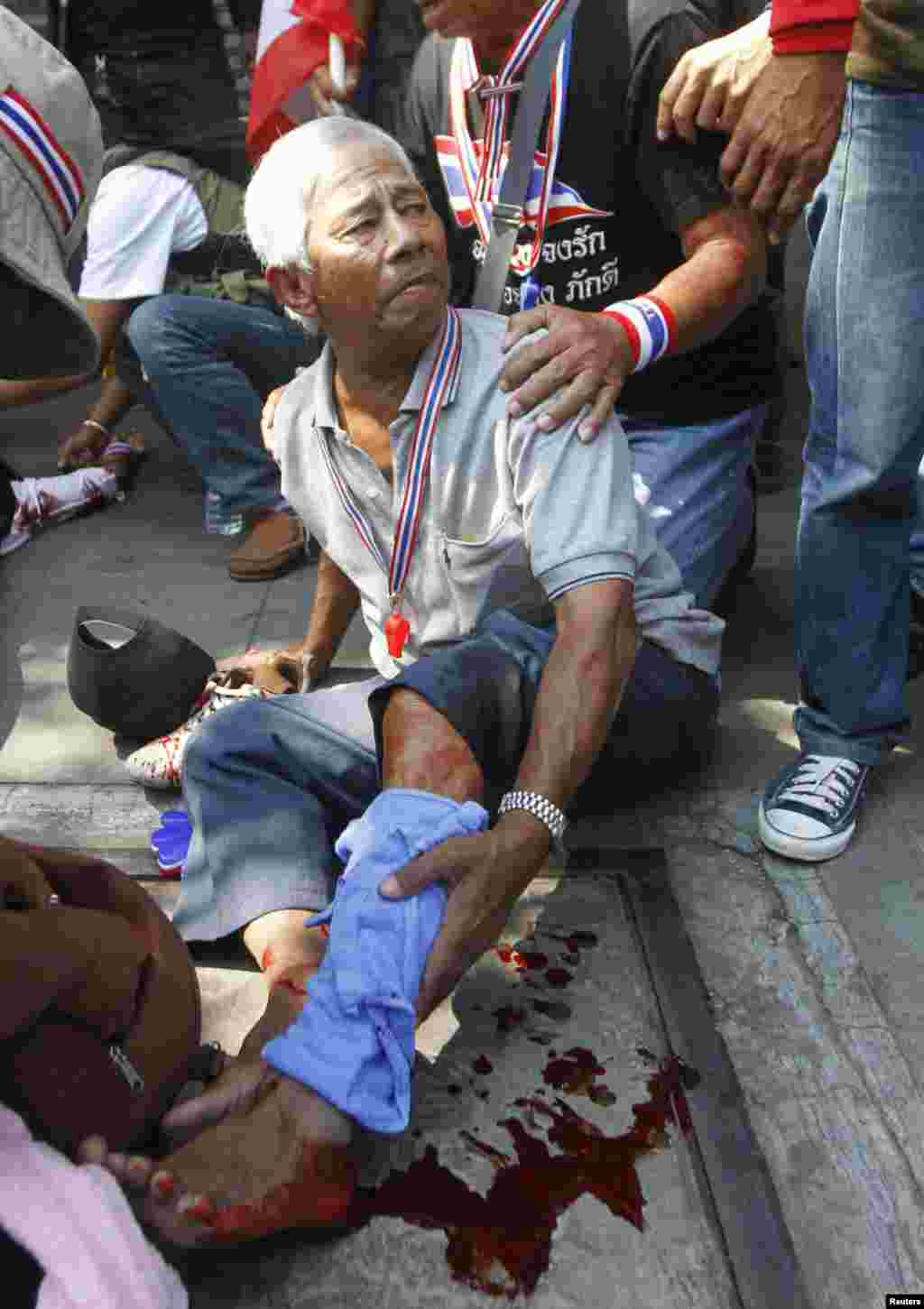 Anti-government protesters help a fellow protester injured in a grenade attack during a rally in Bangkok, Jan. 17, 2014.