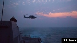 美国海军驱逐舰马斯廷号及其舰载直升机2016年12月5日在南中国海巡逻 (美国海军照片)