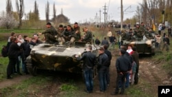 People block a column of Ukrainian Army combat vehicles on their way to the town of Kramatorsk on April 16, 2014.