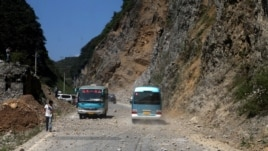 Two buses make their way across a road full of fallen rocks after a series of earthquakes, one of them measuring magnitude 5.7, hit the area near Zhaotong municipality at the border of southwest China's Yunnan and Guizhou province on September 7, 2012.