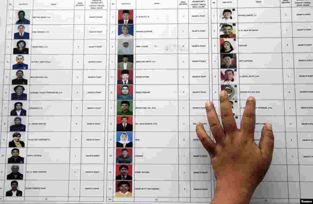 A person places a hand on a list of candidates for members of parliament at a polling station during voting for parliamentary elections in Jakarta, April 9, 2014.