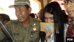 Putri Presiden Joko Widodo, Kahiyang Ayu, dikawal usai menjalani tes calon pegawai negeri sipil di Solo (23/10). (VOA/Yudha Satriawan)
