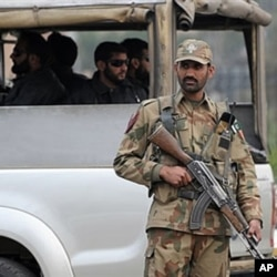 A Pakistani army soldier stands guard at a checkpoint in the garrison city of Rawalpindi, 05 Dec 2009
