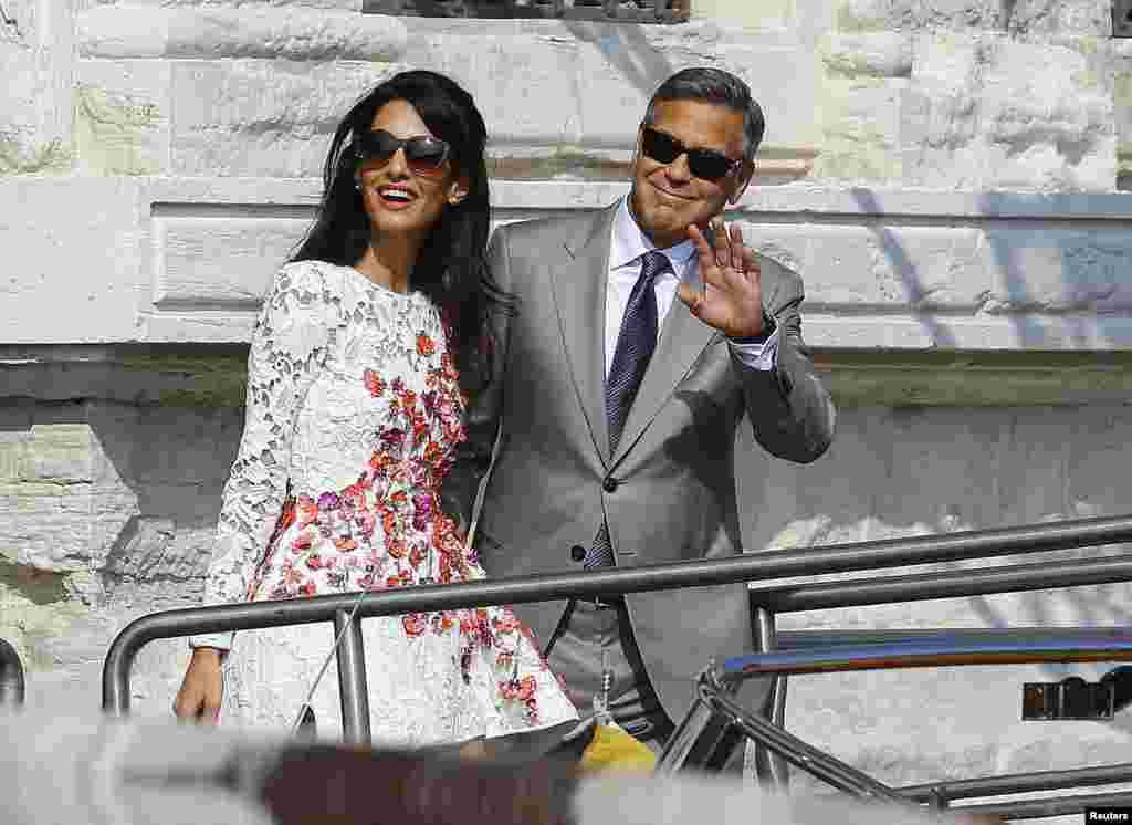 U.S. actor George Clooney and his wife Amal Alamuddin leave the seven-star hotel Aman Canal Grande Venice in Venice, Italy, Sept. 28, 2014.