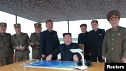 Pemimpin Korea Utara Kim Jong Un saat mengamati uji coba peluncuran rudal balistik jarak jauh dan menengah di Pyongyang. (30/8/17)
