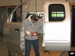 A worker prepares a GMC door to be attached to the lift.
