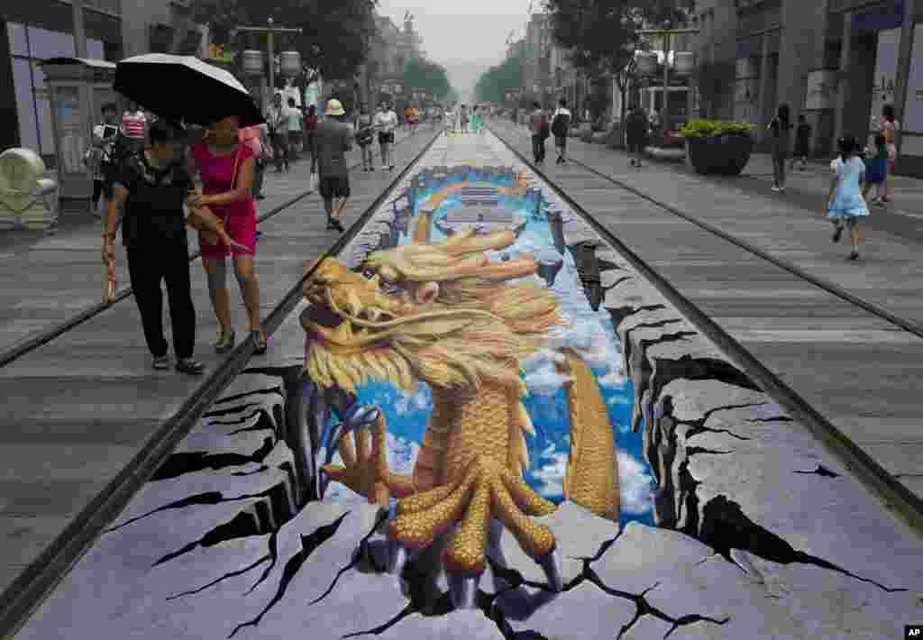 Umjetnost u tri dimenzije - crtež zmaja na asfaltu ulice Qianmen, popularne turističke tačke u Pekingu.